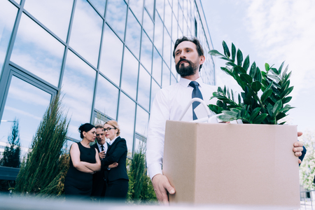 middle aged businessman holding cardboard box while colleagues standing and talking behind