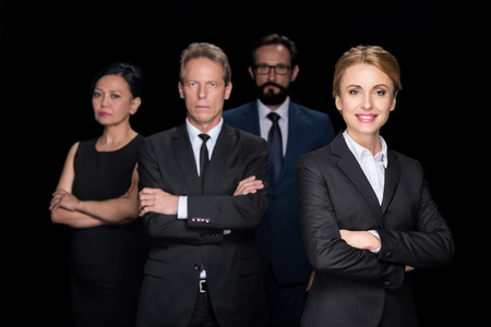 multiethnic group of businesspeople standing with crossed arms and looking at camera isolated on black