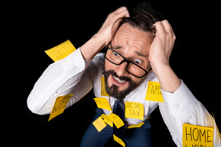 frustrated middle aged businessman with sticky notes on clothes kneeling and tearing hair