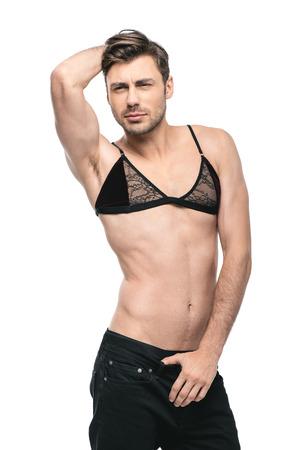 het jonge knappe homoseksuele man stellen in de bustehouder van vrouwen, Stockfoto