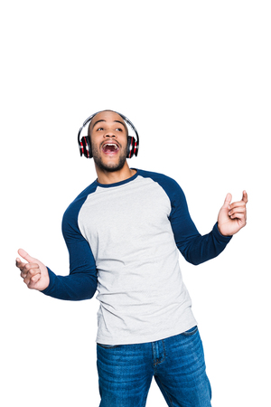 excited african american man listening music in headphones and dancing