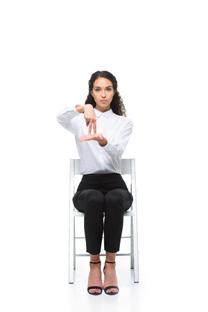 attractive serious woman gesturing signed language while sitting on chair