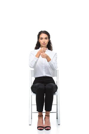 椅子に座りながら手話を身振りで示す魅力的な深刻な女性