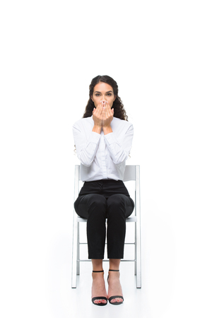 beautiful brunette businesswoman closing mouth with hands while sitting on chair Stock Photo - 85188399