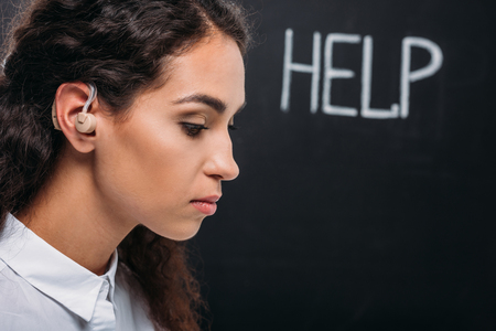 attractive brunette woman with hearing aid, with help word on blackboard Editorial