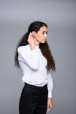 補聴器の魅力的なブルネットの女性 写真素材