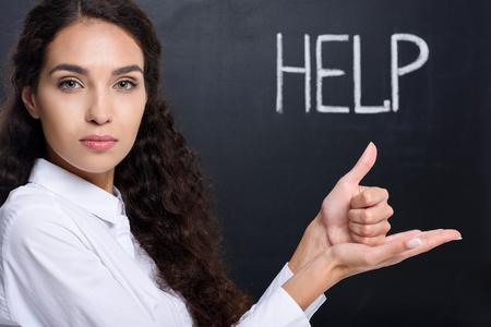 갈색 머리 여자 몸짓으로 서명 된 언어, 칠판에 도움말 단어