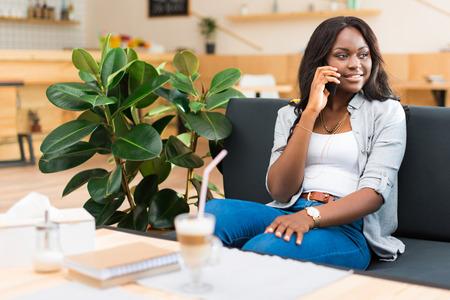 카페에 앉아있는 동안 스마트 폰에 이야기하는 아프리카 계 미국인 여자