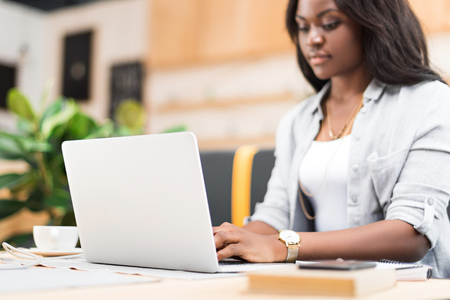 concentrated african american woman using laptop in cafe
