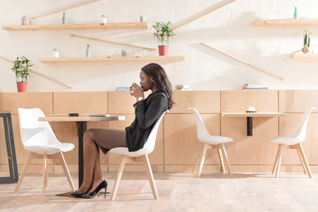 african american woman drinking coffee while sitting in cafe Stock Photo