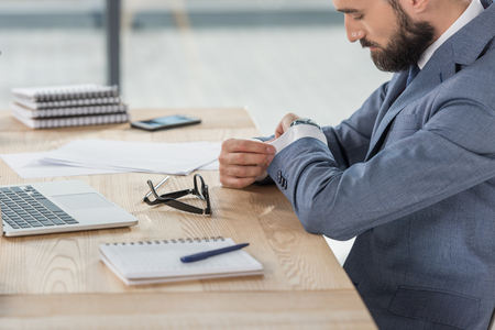 businessman looking at watch on wrist while sitting at workplace in office