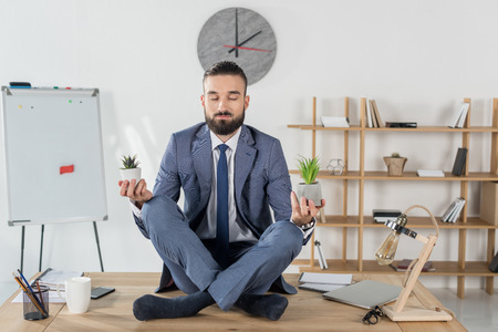 businessman with eyes closed meditating in lotus position while sitting on table in office Banco de Imagens