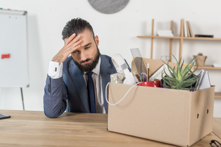 fired upset businessman sitting at workplace with cardboard box with office supplies Stock Photo