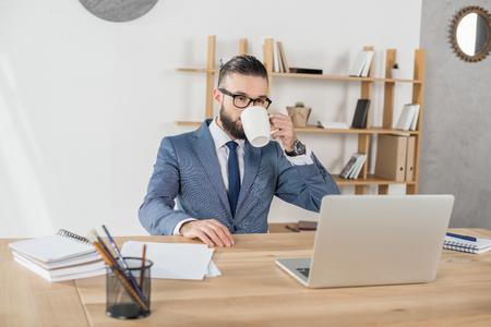 ビジネスマンのオフィスでラップトップで職場で働きながらコーヒーを飲む