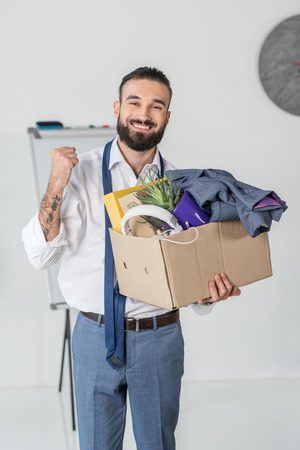 smiling businessman with cardboard box in hands quitting job