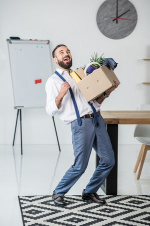 businessman with cardboard box in hands quitting job
