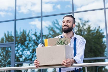 オフィスビルの外に立った手で事務用品を備えたダンボール箱を持ったビジネスマン、仕事のコンセプトをやめる