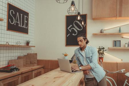 jonge winkeleigenaar die laptop met behulp van terwijl binnen het werken
