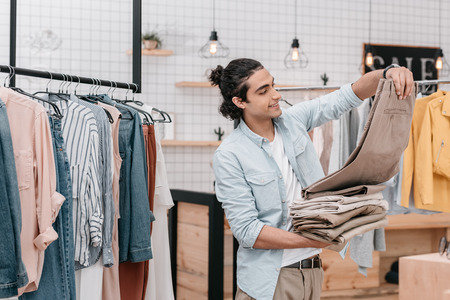 business owner holding pile of pants while working in boutique before opening