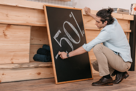 male seller drawing fifty percent discount sign on chalkboard