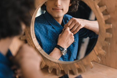 young man buttoning shirt and looking at mirror Stock Photo