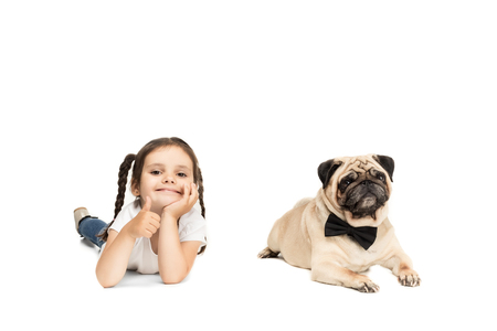 little adorable girl showing thumb up while lying with pug dog in bow tie