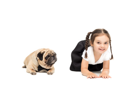 happy adorable girl playing with pug dog, isolated on white