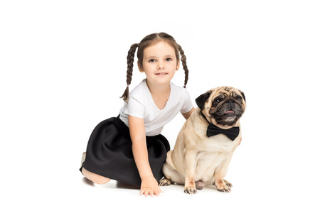 happy adorable girl hugging pug dog in bow tie, isolated on white