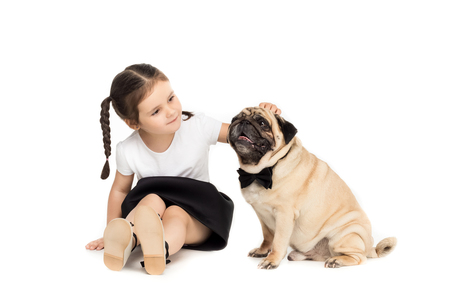 little happy adorable girl playing with pug dog in bow tie, Stock Photo