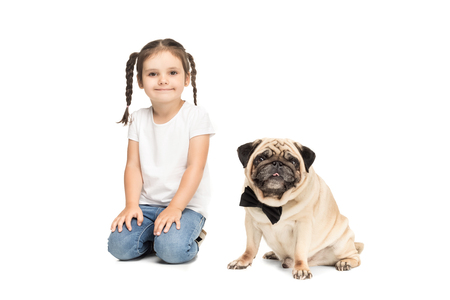 little happy adorable girl sitting with pug dog in bow tie