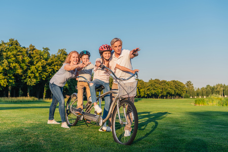 gesturing: grandparents helping children ride bicycle
