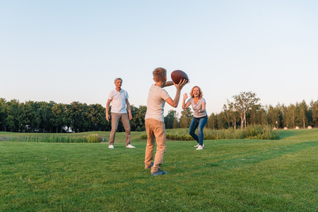kid playing rugby with grandparents Stock Photo