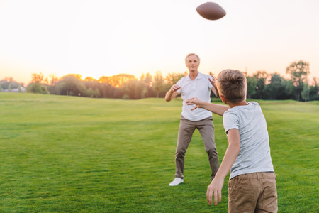 grandfather and grandson playing rugby Stock Photo