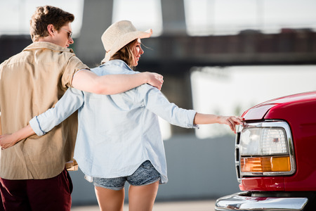 young couple walking near car Stock Photo