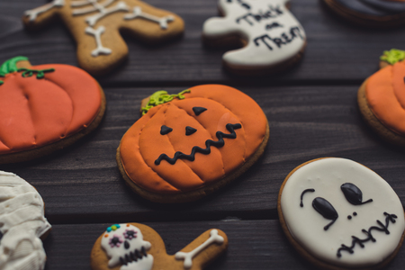 composition of halloween cookies on black table
