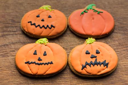 composition of halloween pumpkin cookies on wooden board