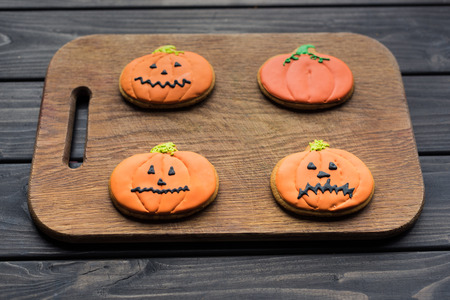 composition of homemade halloween cookies on wooden cutting board Stock Photo