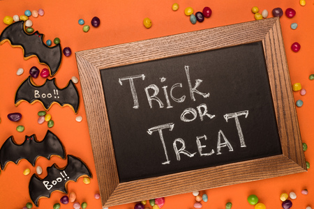 top view of chalkboard with trick or treat inscription on orange table with sweets