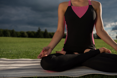 cropped shot of woman practicing lotus pose while meditating alone Stock Photo