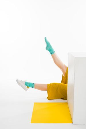 female legs behind white cube