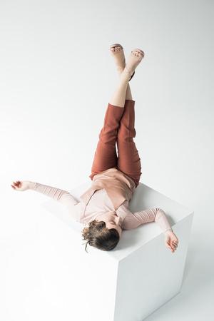 stylish girl laying on white cube Stock Photo