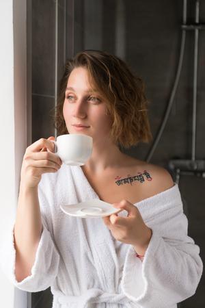 コーヒーを飲みながらバスローブの女の子 写真素材