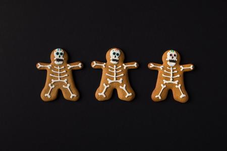 top view of halloween skeleton cookies isolated on black