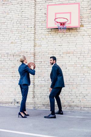 business people playing basketball