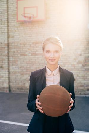 businesswoman holding basketball ball