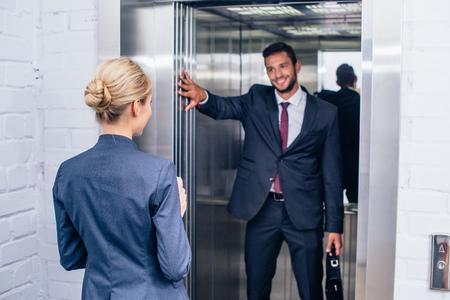 여자 엘리베이터 문을 들고 사업가