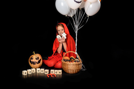 child in halloween costume with sweets