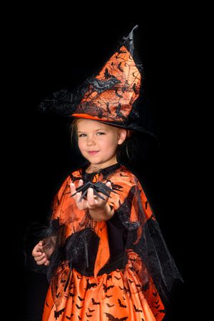 child in halloween costume of witch holding spider, isolated on black