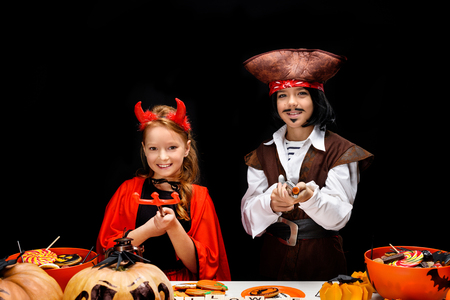 children in halloween costumes of devil and pirate Stock Photo