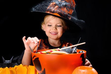 Pequeña bruja con dulces de halloween Foto de archivo - 85818767
